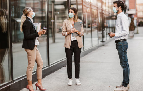 People in face masks talking while social distancing during COVID pandemic
