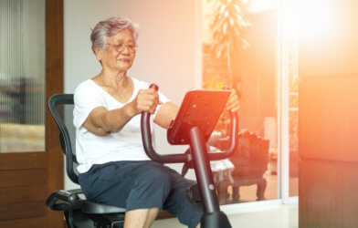 Older senior women using exercise bike