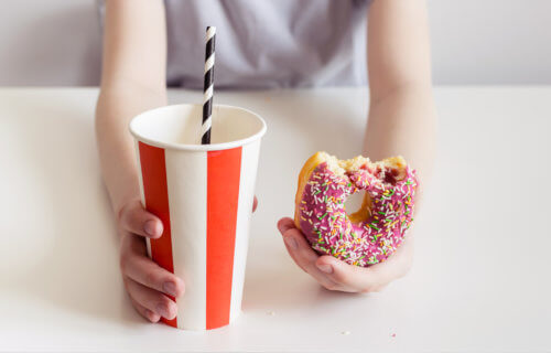 Child holding sugary, processed junk food