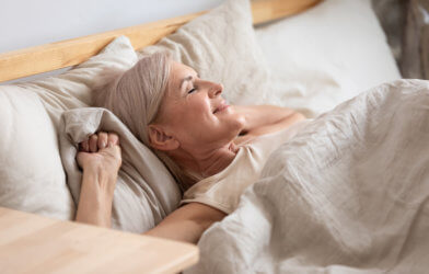 Older woman waking up in bed happy, rested from good night of sleep