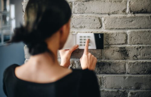 Woman turning on home alarm security system
