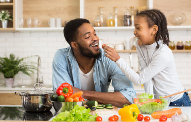 Daughter feeding her dad some vegetables while making a salad