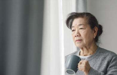 Older woman looking out window, alone, sad