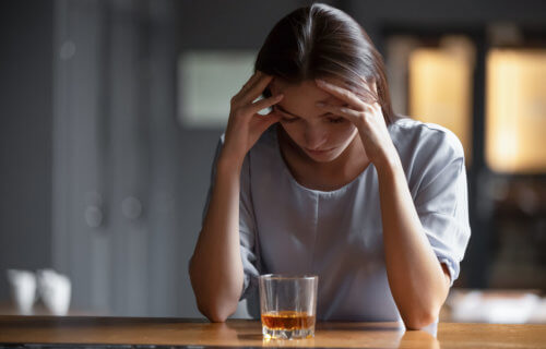 Woman drinking alcohol alone, stressed, depressed