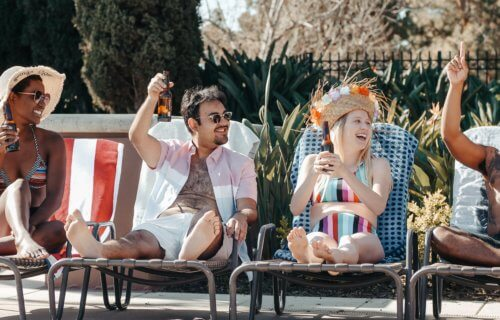 Friend having drinks by the pool, enjoying summer vacation