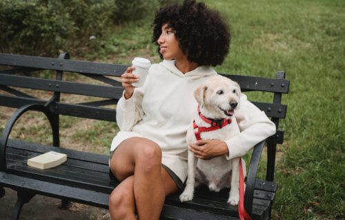 Woman sitting outside on park bench with dog while drinking coffee
