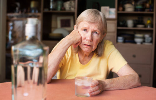 Older woman drinking alcohol alone