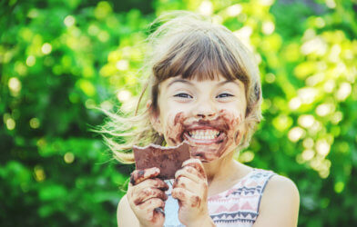 Little girl eating chocolate candy bar