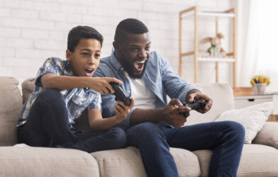Father, son playing video games together