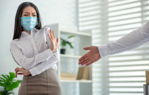 Woman in mask won't shake hand during COVID pandemic