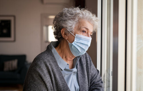 Older woman wearing face mask looking out window, sad, alone during COVID pandemic