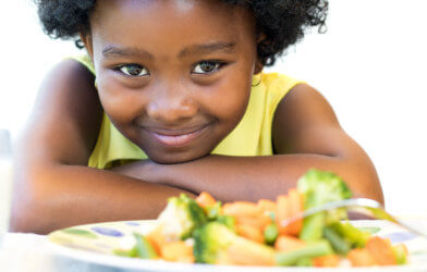 Cute little girl smiling while eating plate of vegetables