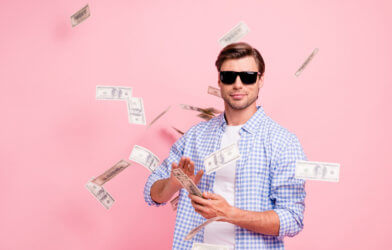 Man throwing money into the air like he's rich