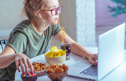 Woman eating snacks and junk food while working at desk
