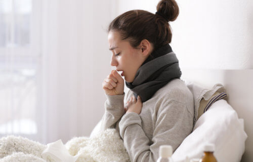 Woman sick in bed with cold, cough, COVID symptoms