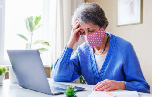 Woman in face mask experiencing COVID-19 symptoms while working