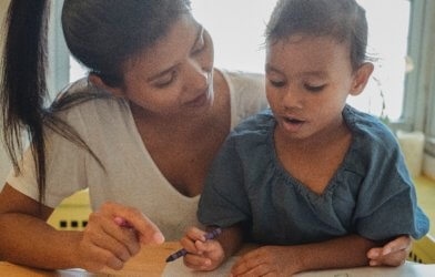 Mother coloring, reading with young child