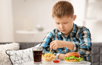 Child eating fast food at home