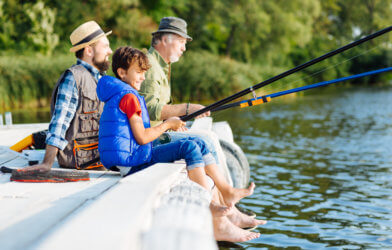 Boy fishing with his father and grandfather