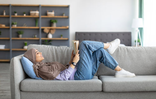 Muslim woman reading on couch