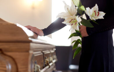 Mourner touching casket at funeral