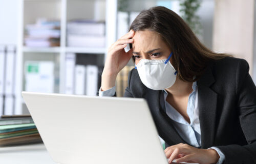 Woman in mask stressed, upset while looking at computer