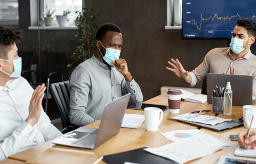Employee with mask on coughing during work meeting